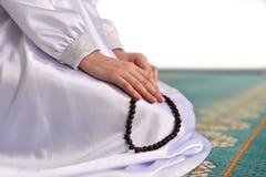 Vrouw die een rozentuin houden en in een witte kleding in een moskee op een witte achtergrond bidden stock afbeelding
