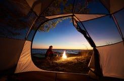 Vrouw die een rust hebben bij nacht die dichtbij toeristentent kamperen, kampvuur op overzeese kust onder sterrige hemel royalty-vrije stock afbeelding