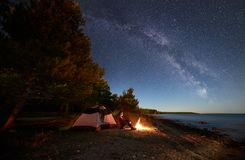 Vrouw die een rust hebben bij nacht die dichtbij toeristentent kamperen, kampvuur op overzeese kust onder sterrige hemel stock fotografie