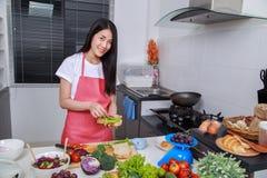 Vrouw die een sandwich in keukenruimte voorbereiden stock afbeeldingen