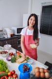 Vrouw die een sandwich in keukenruimte voorbereiden stock foto's