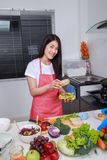 Vrouw die een sandwich in keukenruimte voorbereiden stock afbeelding