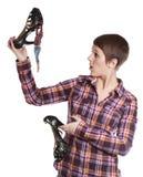 Vrouw die een schoen houden die door een uiterst klein meisje wordt beklommen stock fotografie