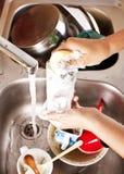 Vrouw die een schotel wast Stock Foto's