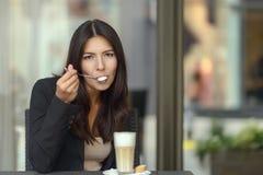 Vrouw die een smakelijke kop van cappuccinokoffie genieten van stock afbeeldingen