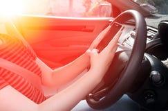 Vrouw die een smartphone gebruiken terwijl het drijven van auto tussen het drijven omdat verslaafden sociale media stock afbeelding