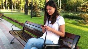 Vrouw die een smartphone in het park gebruiken stock videobeelden