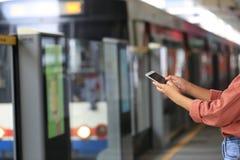 Vrouw die een smartphone op BTS-hemeltrein gebruiken op de achtergrond van Bangkok, Thailand, Communicatietechnologieconcept stock afbeelding
