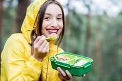 Vrouw die een snack in het bos hebben stock afbeelding