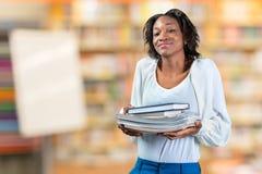 vrouw die een stapel van boeken houden Stock Afbeelding