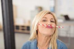 Vrouw die een stro in evenwicht brengen haar lip Stock Foto