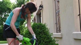 Vrouw die een struik en het tuinieren triming stock footage