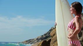 Vrouw die een Surfplank houden stock footage