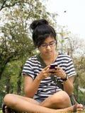Vrouw die/een tekstbericht/een e-mail verzendt ontvangt Stock Foto's
