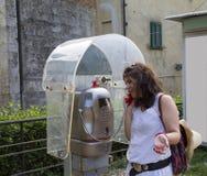 Vrouw die in een telefooncel spreken Stock Foto