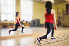Vrouw die een training met domoren doen bij de gymnastiek Stock Foto