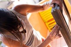 Vrouw die een venster met zand oppoetsen stock afbeeldingen
