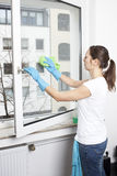 Vrouw die een venster schoonmaakt Stock Afbeelding