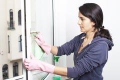 Vrouw die een venster schoonmaakt Stock Fotografie