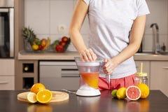 Vrouw die een vers gedrukte grapefruit juice maken royalty-vrije stock fotografie