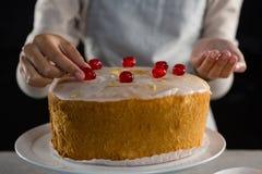 Vrouw die een verse gebakken cake met kers toping stock foto's