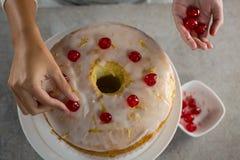 Vrouw die een verse gebakken cake met kers toping royalty-vrije stock fotografie
