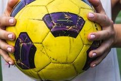 Vrouw die een voetbalbal in haar handen houden stock afbeeldingen