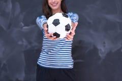 Vrouw die een voetbalbal voor krijttekenbord houden Stock Afbeeldingen