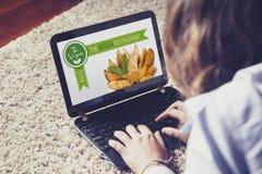 Vrouw die een website bezoeken die van het veganistrestaurant thuis liggen Stock Afbeelding