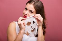 Vrouw die een weefselmasker toepassen royalty-vrije stock foto