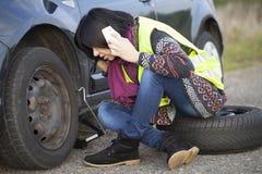 Vrouw die een wiel op een auto op de lege weg veranderen Royalty-vrije Stock Foto