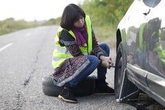 Vrouw die een wiel op een auto op de lege weg veranderen Royalty-vrije Stock Afbeelding