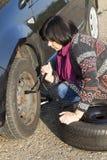 Vrouw die een wiel op een auto op de lege weg veranderen Stock Foto's
