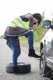 Vrouw die een wiel op een auto op de lege weg veranderen Royalty-vrije Stock Fotografie