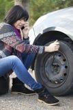 Vrouw die een wiel op een auto op de lege weg veranderen Royalty-vrije Stock Foto's