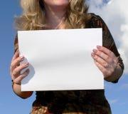 Vrouw die een witte kaart houdt stock foto