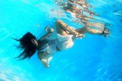 Vrouw die een witte kleding draagt onderwater Stock Afbeelding
