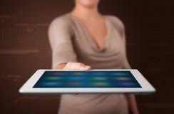 Vrouw die een witte tablet met onscherpe apps houden Stock Foto