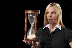 Vrouw die een zandtijdopnemer houdt Stock Foto