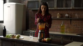 Vrouw die eigengemaakte smoothie in keuken mengen stock footage