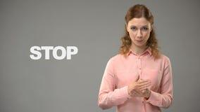 Vrouw die einde in gebarentaal, tekst op achtergrond, mededeling voor doof zeggen stock video