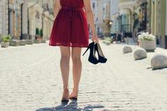 Vrouw die in elegante rode kleding haar hoge hielschoenen in handen houden stock foto