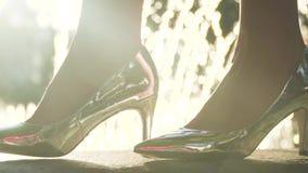 Vrouw die in elegante zilveren schoenen op hoge hielen dichtbij fonteinen lopen stock videobeelden