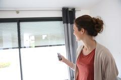 Vrouw die elektrische blinden openen royalty-vrije stock foto