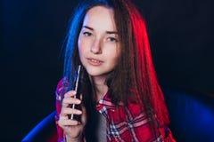 Vrouw die elektronische sigaret met rook roken stock fotografie