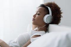 Vrouw die en aan muziek ontspant luistert stock fotografie