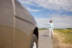 Vrouw die en auto met omhoog duimen liften tegenhouden Royalty-vrije Stock Foto's