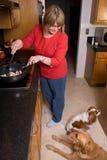 Vrouw die en bij h kookt glimlacht stock foto's