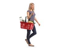 Vrouw die en een het winkelen mand lopen dragen Royalty-vrije Stock Afbeelding