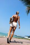 Vrouw die en een longboard lopen houden Royalty-vrije Stock Afbeelding